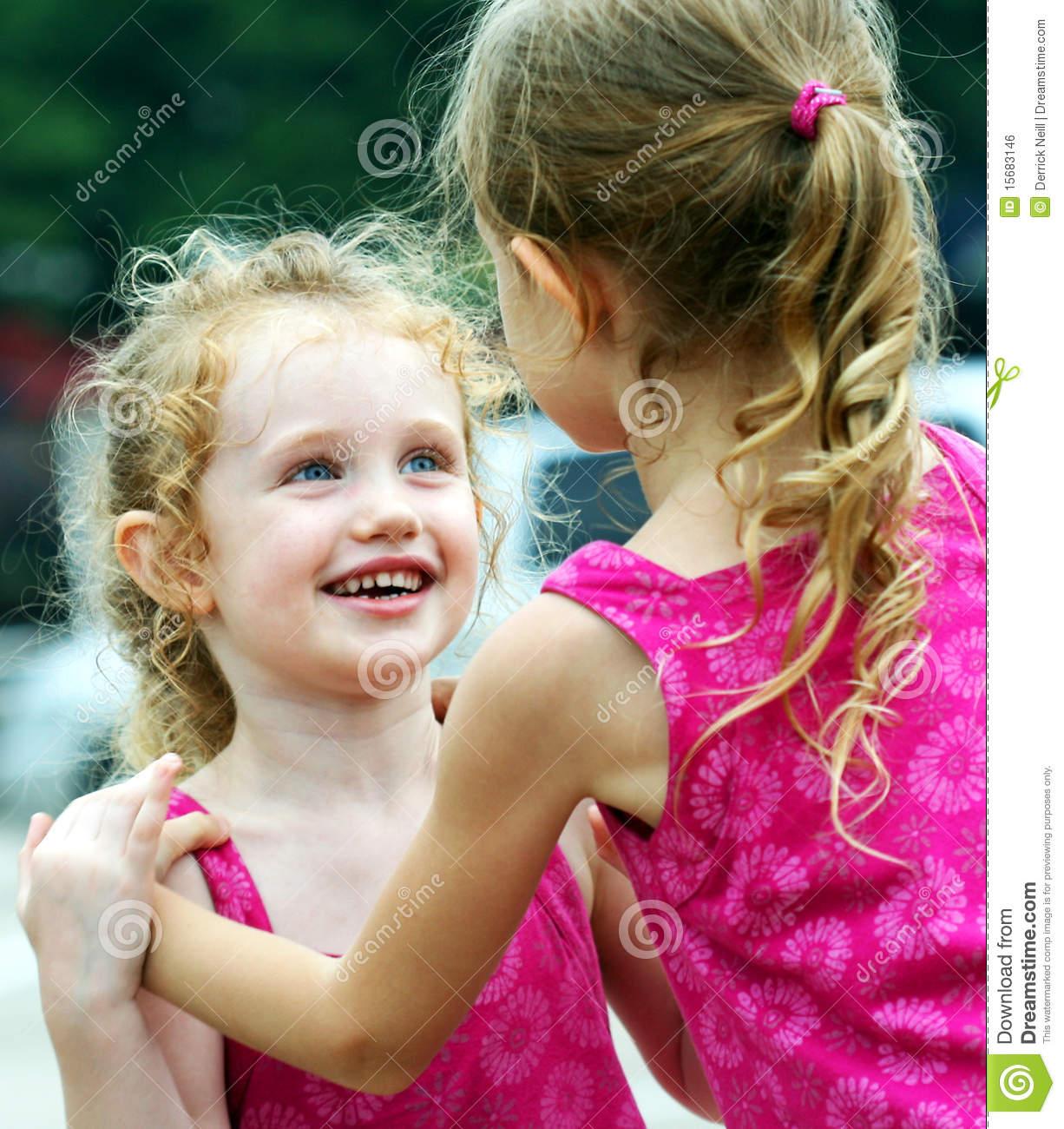 Una niña sonríe Adoringly en su hermana