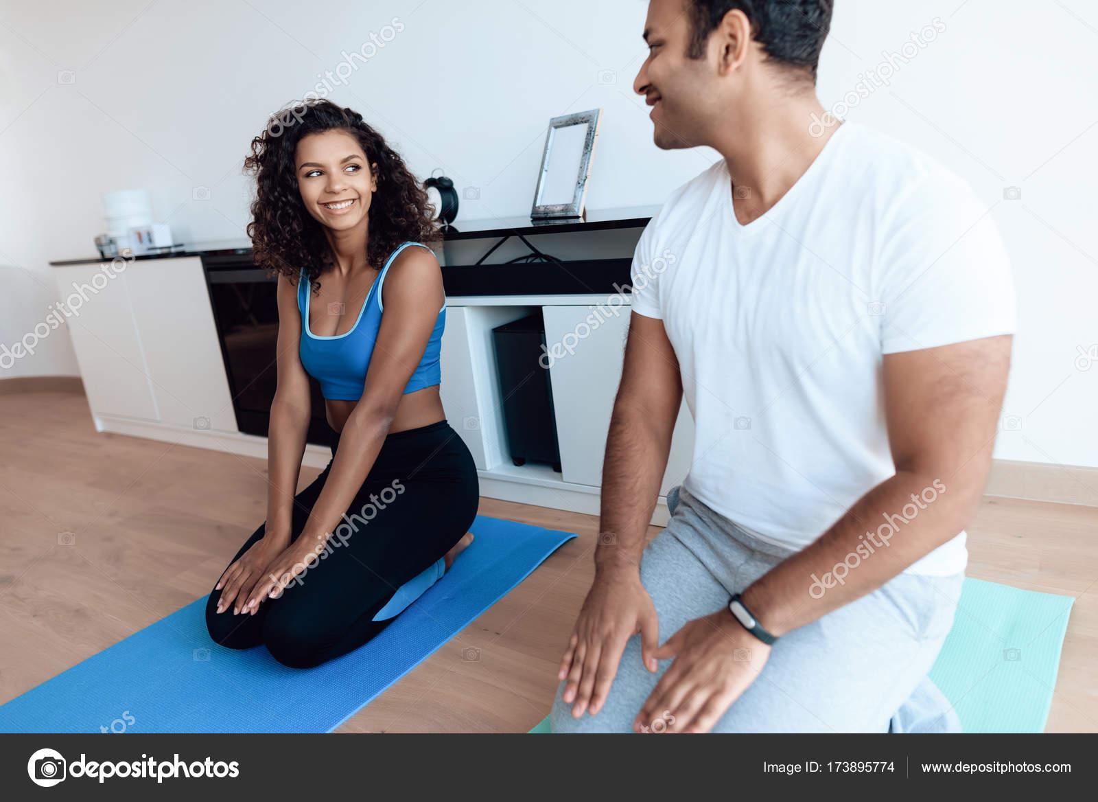 Aframerican pareja haciendo ejercicios de yoga en casa. Se sientan en el  piso en colchonetas