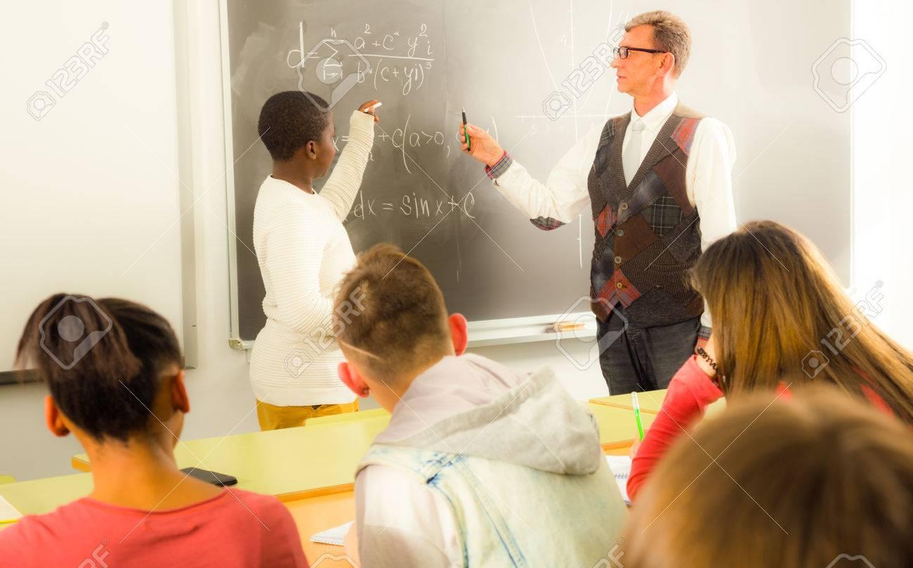 Foto de archivo - Ordinaria Aframerican muchacho del estudiante responde a  cerca de la pizarra en clase de matemáticas