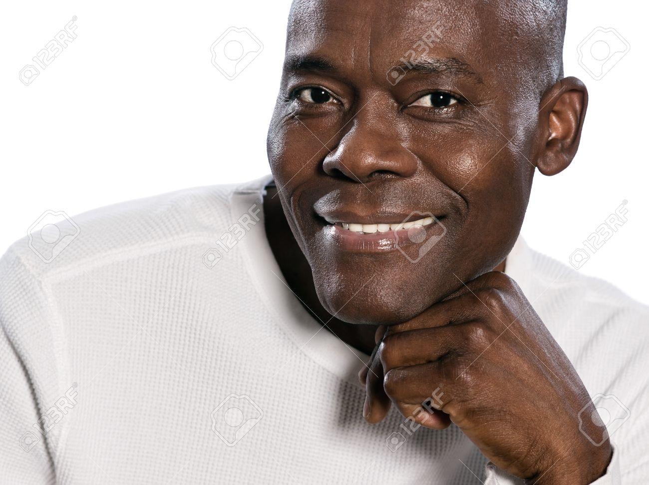 Close-up portrait of an afro American mature man smiling with hand on chin  in