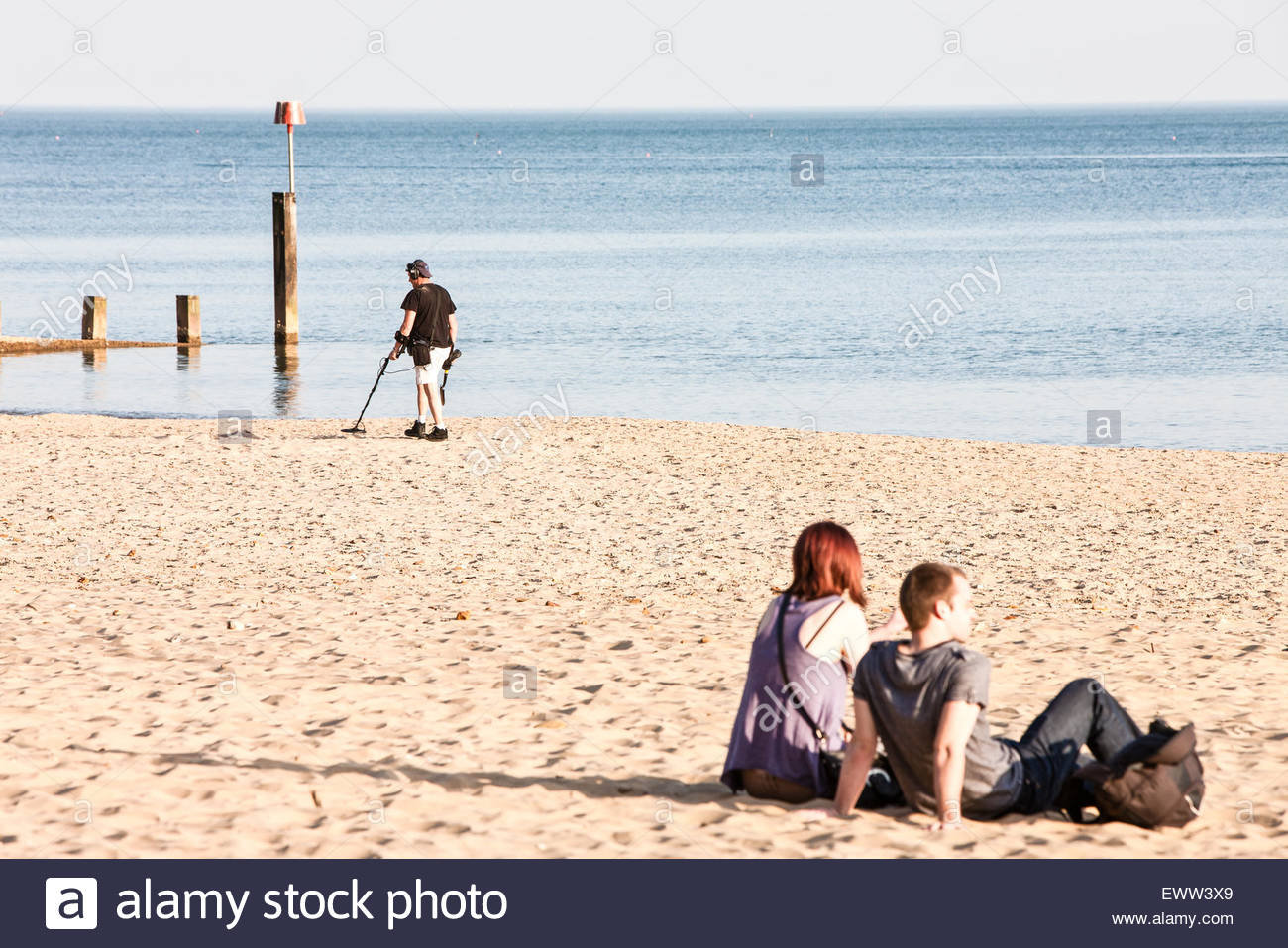 On a sunny Spring day using metal detector after most tourists/holiday  makers have left beach looking for lost items/treasure