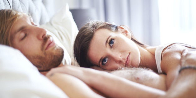 Pensive woman laying on sleeping man on bed