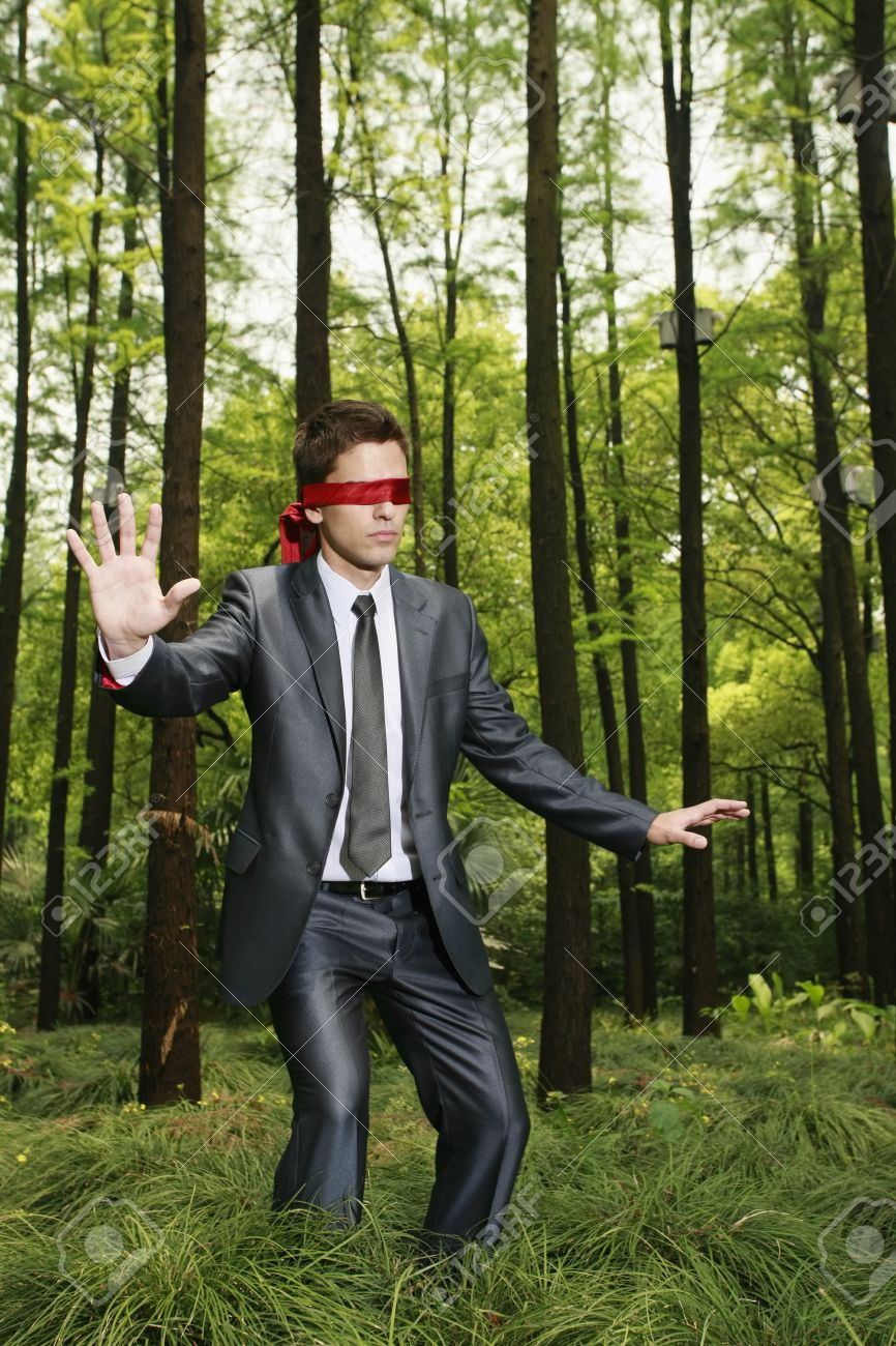 Businessman with blindfold walking aimlessly in the forest Stock Photo -  8149416