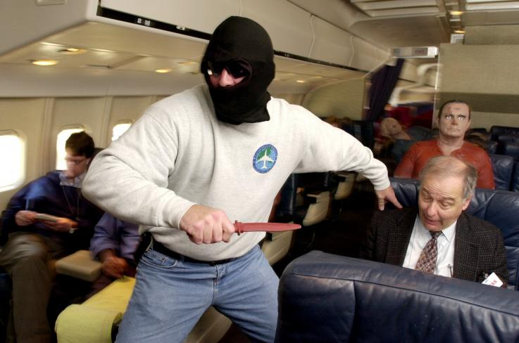 A knife-wielding sky marshal runs between seats during a simulated  hijacking aboard a retired L-1011 aircraft at the Federal Aviation  Administration (FAA)