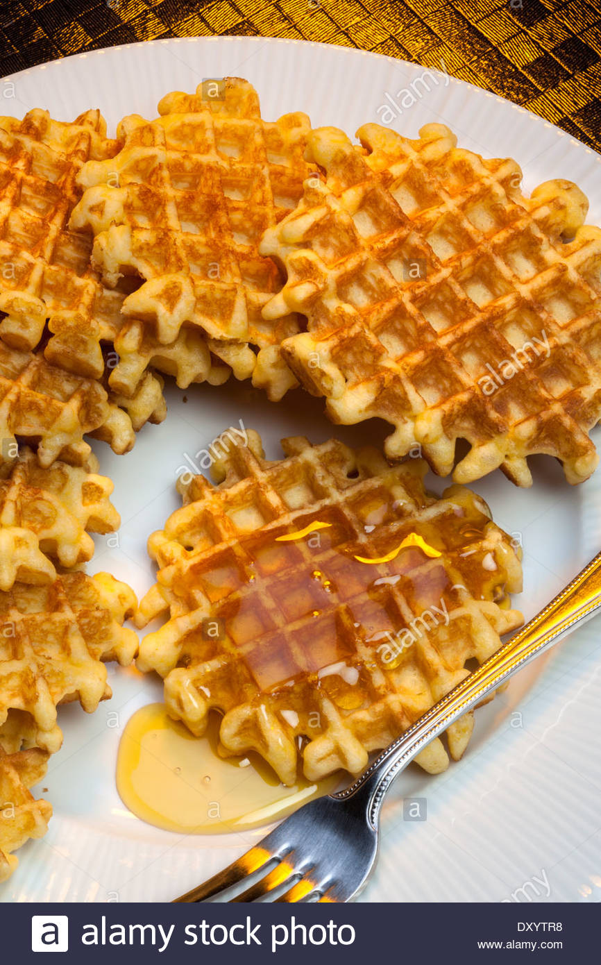 Waffles are mall crisp batter cake, baked in a waffle iron and eaten hot  with butter or syrup.
