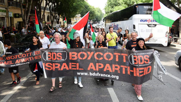 FILE PHOTO: Protesters march behind a banner of the BDS organization in  France, June