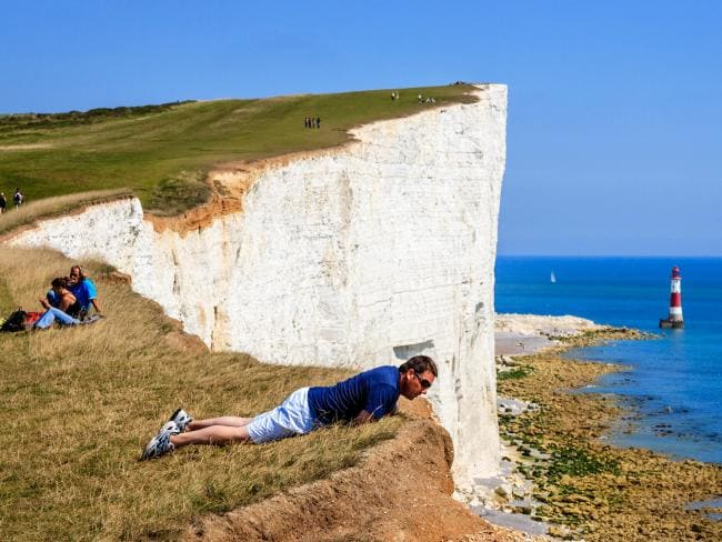 A man leans over the edge at Beachy Head. Picture: Alamy