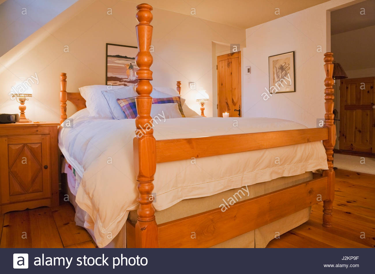 Queen size bed on wooden frame with tall bedposts in master bedroom on the  upstairs floor inside a Canadiana cottage style log home.