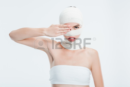 Stock Photo - woman with bandages after plastic surgery hiding eye behind  hand isolated on white