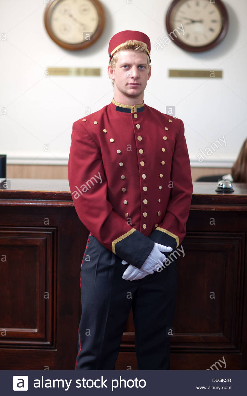 Bellhop standing in hotel lobby - Stock Image