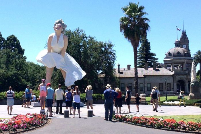 People look at a three-storey statue of Marilyn Monroe, erected in a town