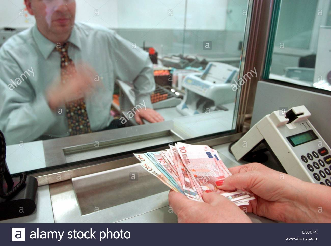 (dpa) - A customer in front of a bank teller window deposits cash money in  her account at a branch of the Hamburg savings bank in Hamburg, Germany,