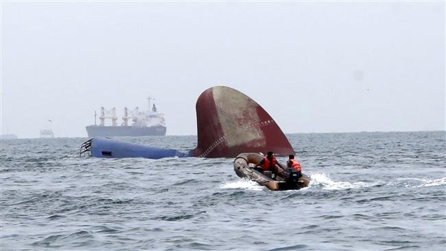 An Indonesia rescue team approaches a freighter, which was cast adrift  after colliding with a