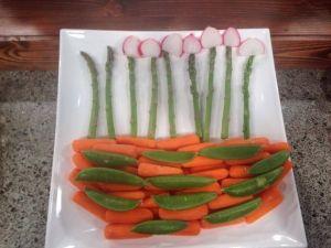 Flower veggie platter asparagus topped w/ sliced radishes green bean topped  w/ tiny tomato rose thin sliced celery stalk w/ cauliflowerette