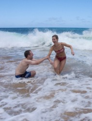 Two people cavorting in the waves.