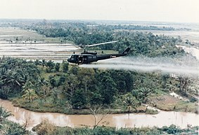 U.S. Army Huey helicopter spraying Agent Orange over agricultural land  during the Vietnam War.