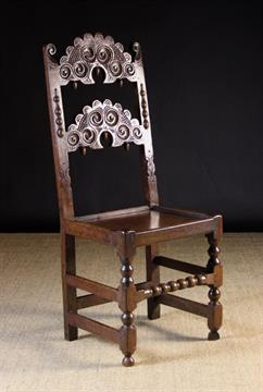 A Good 17th Century Carved Oak Derbyshire Chair. The scalloped dome topped  back bars carved with