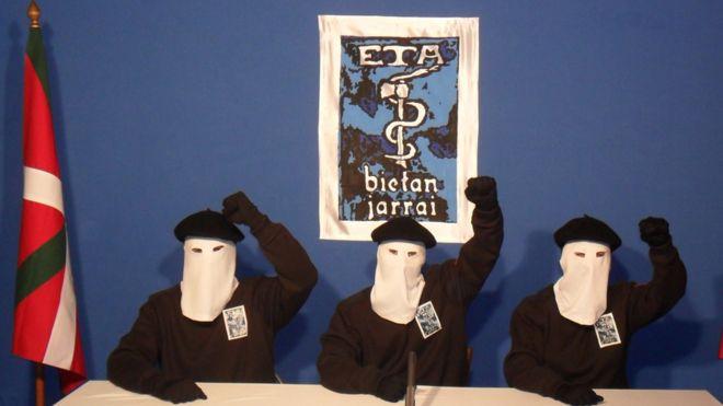 Militantes de ETA enmascarados con el puño izquierdo en alto frente al  escudo de la organización