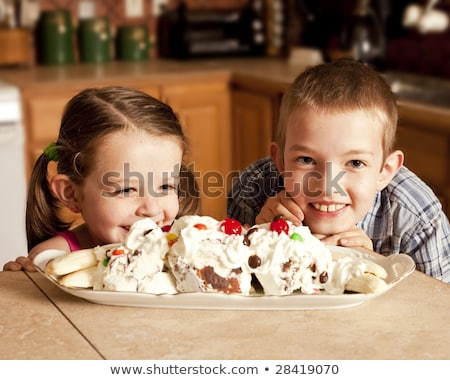 two kids eagerly waiting to eat ice cream