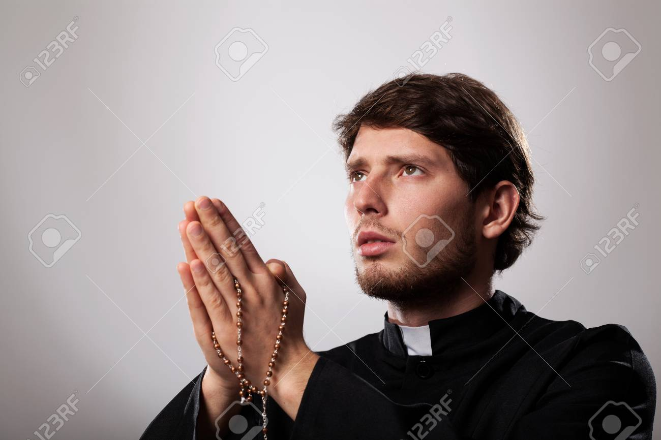 Stock Photo - Young priest is earnestly praying the rosary