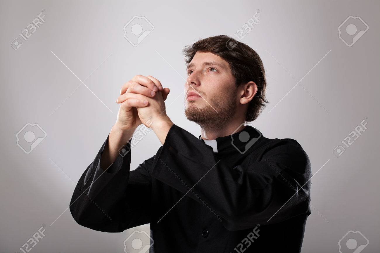 Stock Photo - Young christian priest is earnestly praying to god