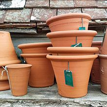 Terracotta flower pots with terracotta tiles in the background
