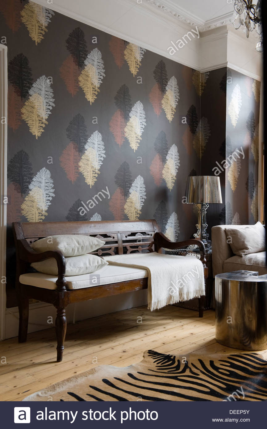 Leaf motif wallpaper with metallic accents in eclectically furnished living  area