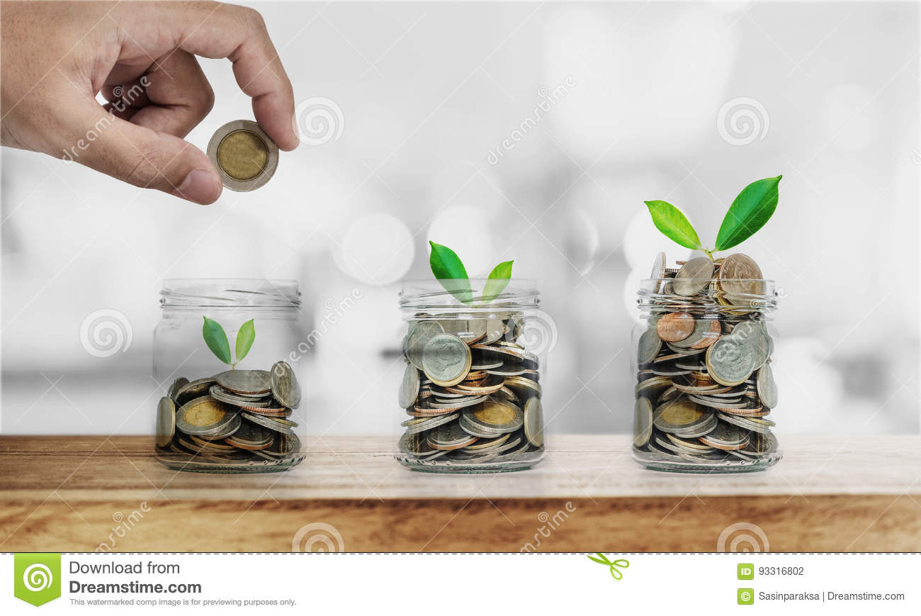 Hand putting coin in glass bottles with plants glowing, Saving money ,  investment and economize