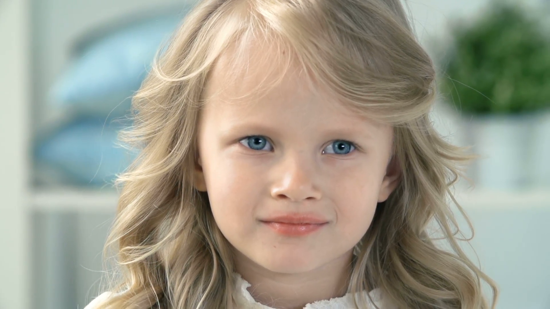 Head and shoulders of little pretty fair-haired girl looking at camera  Stock Video Footage - Storyblocks Video