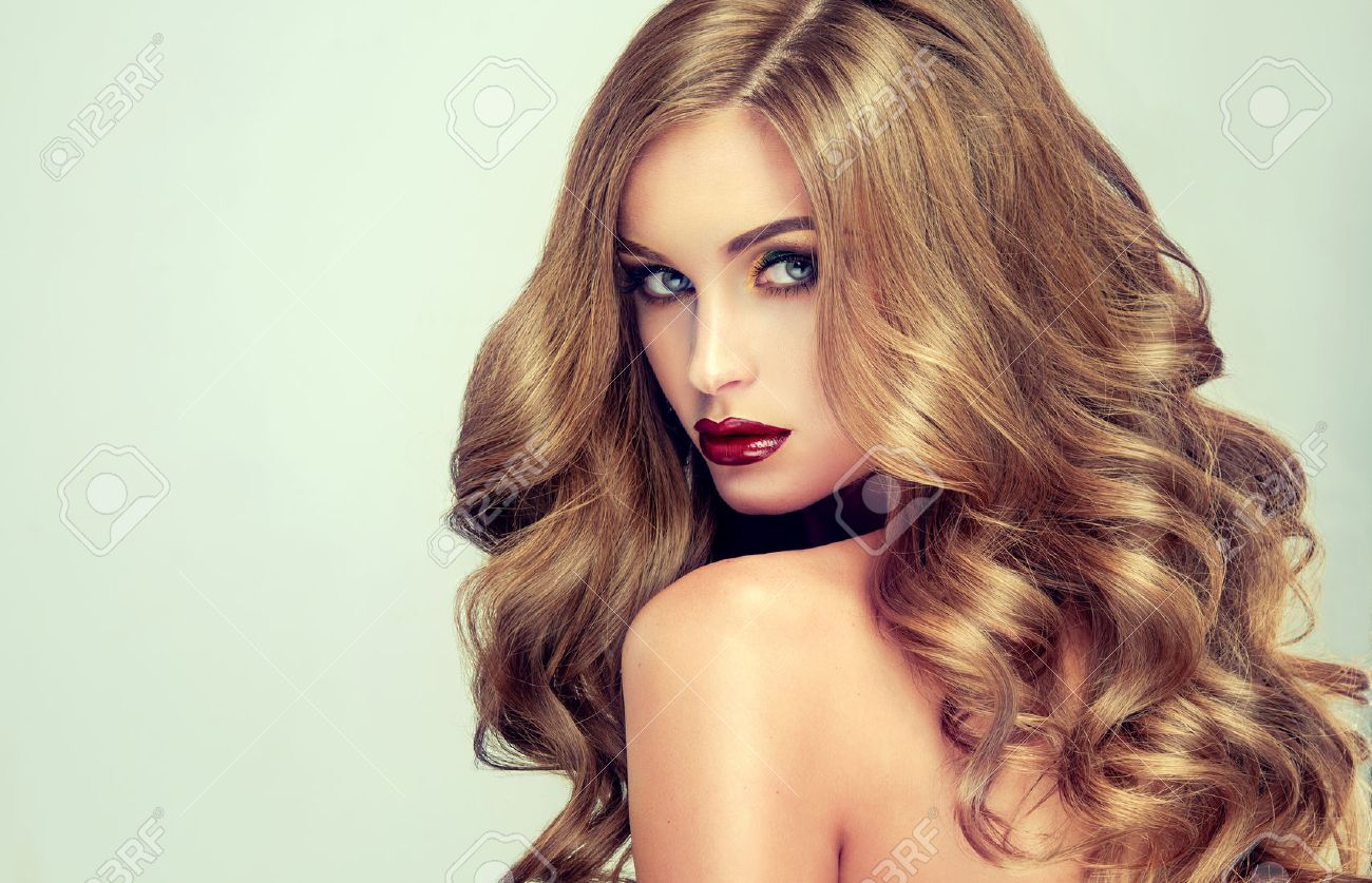 Beautiful girl with long wavy hair . fair-haired model with curly hairstyle  and fashionable