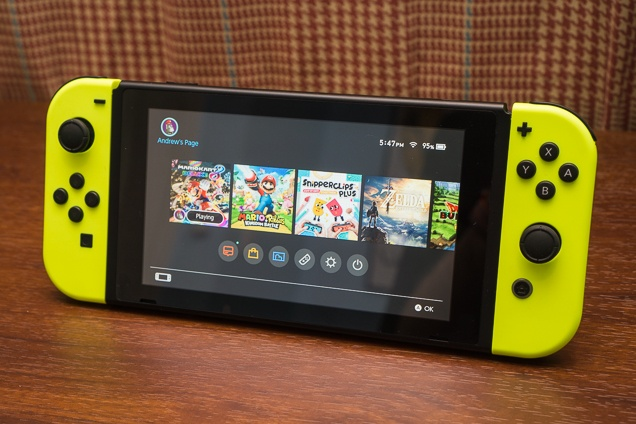 A Nintendo Switch with bright yellow Joy-Cons sitting on a table, with its