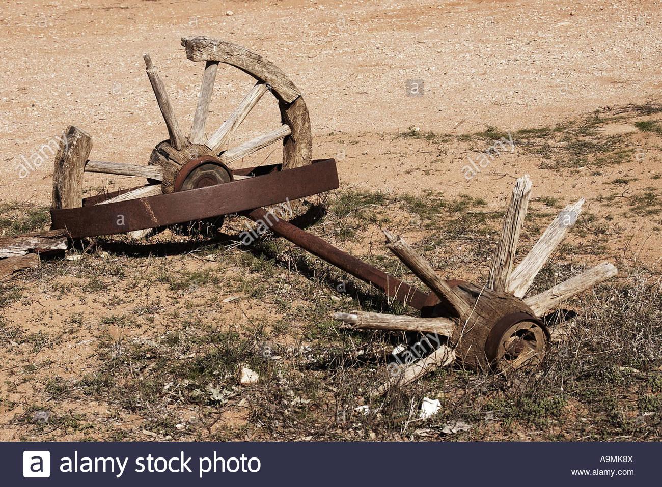 broken cart wheels half buried in dirt