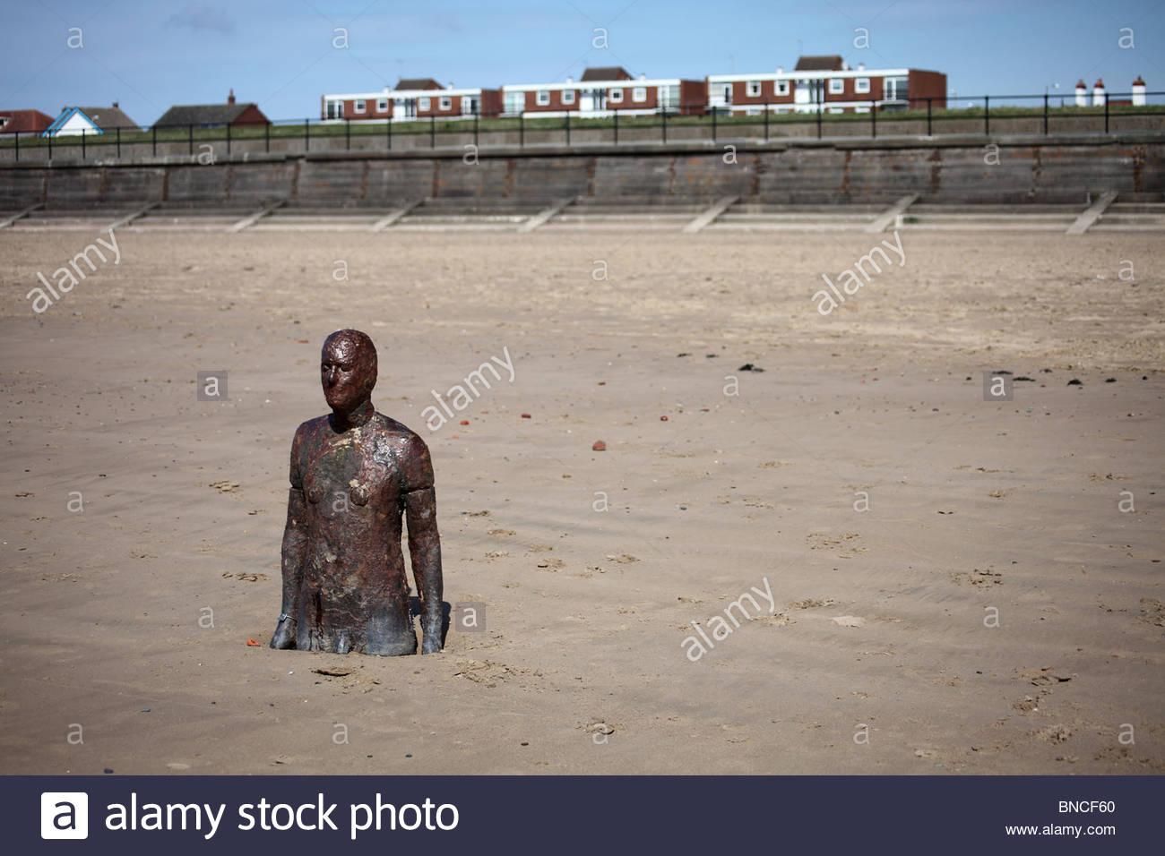Half-buried Antony Gormley cast-iron sculpture on Crosby Beach, Sefton,  Liverpool