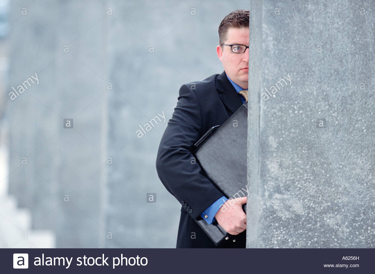 conceptual image of businessman half concealed by wall holding a briefcase  to his chest
