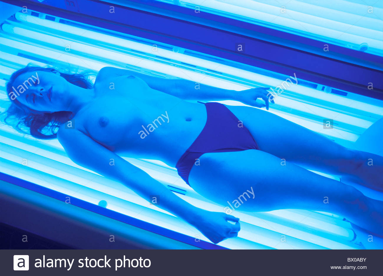 Beauty radiotherapy browning woman half-naked half-covered lie neon tubes  take it easy relax solarium sun