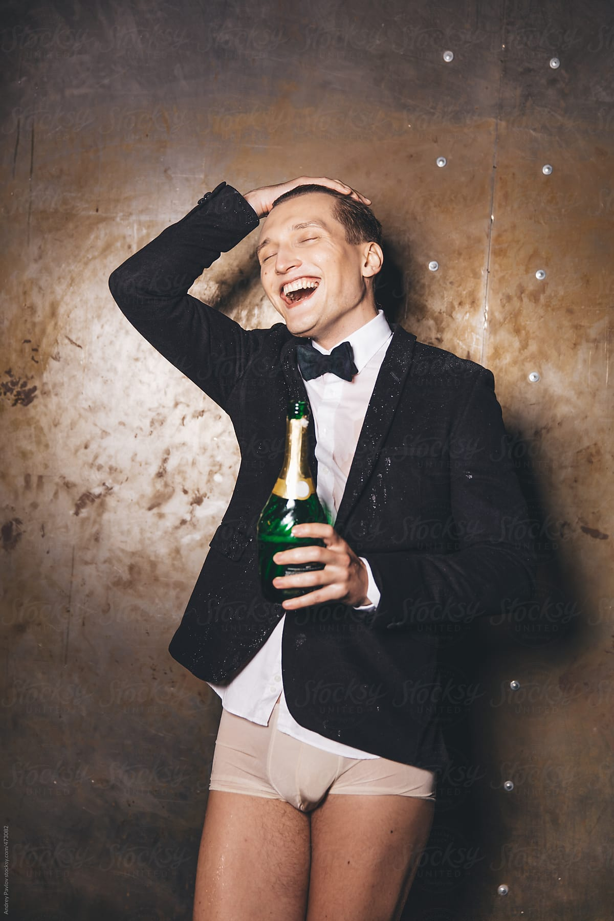 Half-dressed men in a suit holding bottle of champagne and laugh by Andrey  Pavlov