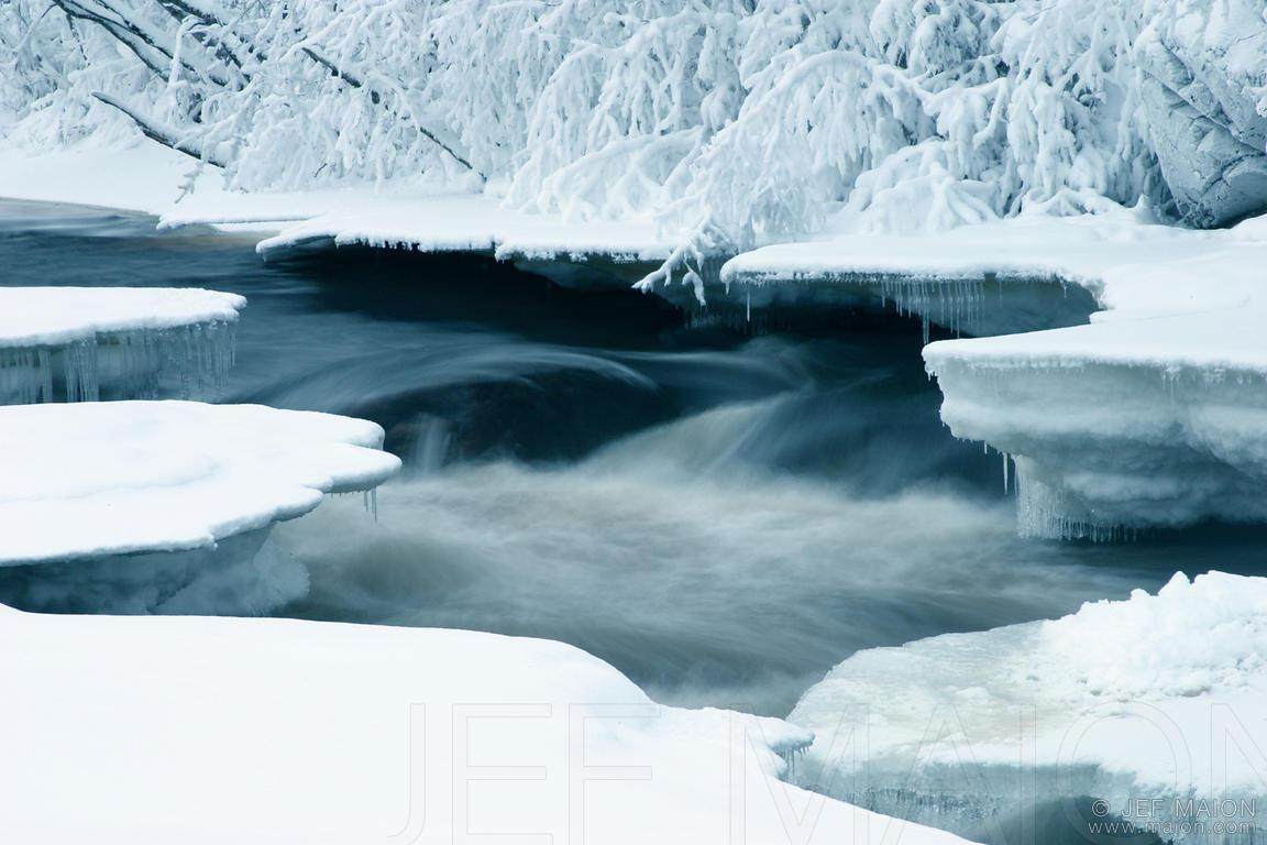 Half-frozen river in snow