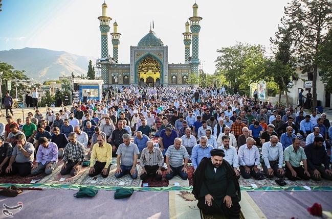 Group of Muslims kneeling in prayer, daytime, outdoors