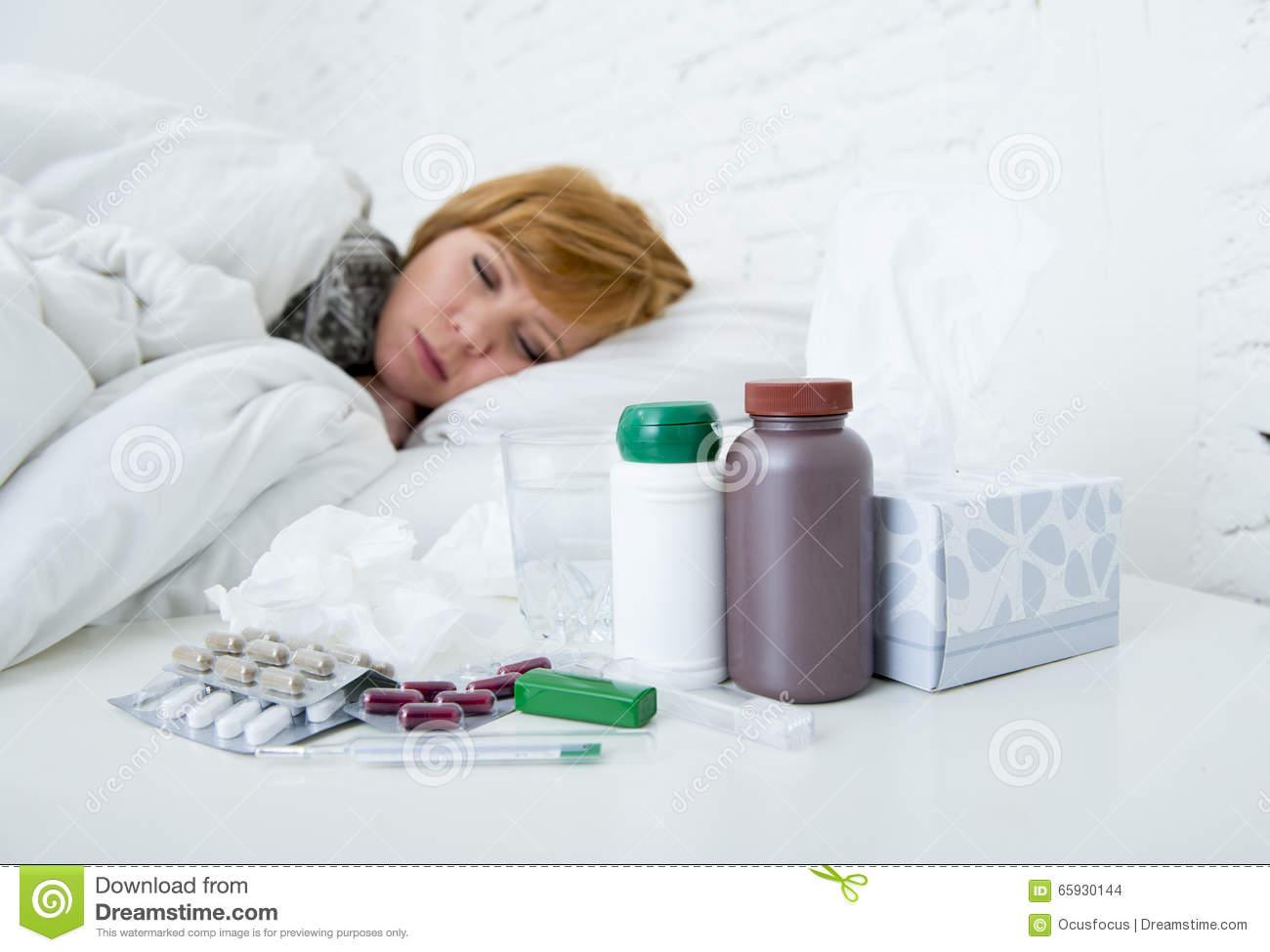 Sick woman feeling bad ill lying on bed suffering headache winter cold and  flu virus having