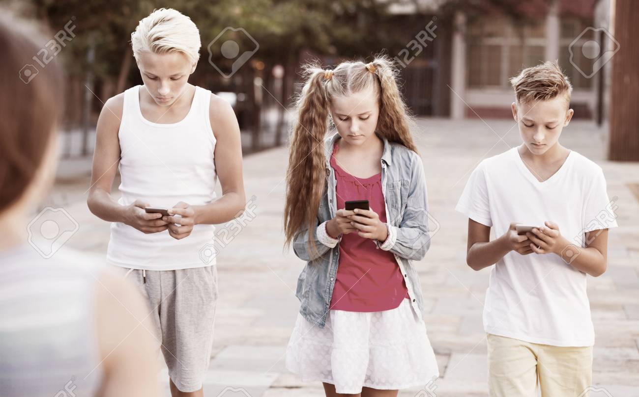 Stock Photo - Three cheerful children keened on mobile phones during joint  walk around city