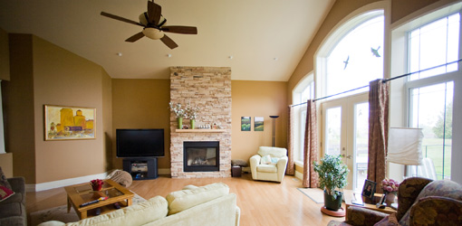 Living room with sunny windows and paddle ceiling fan.
