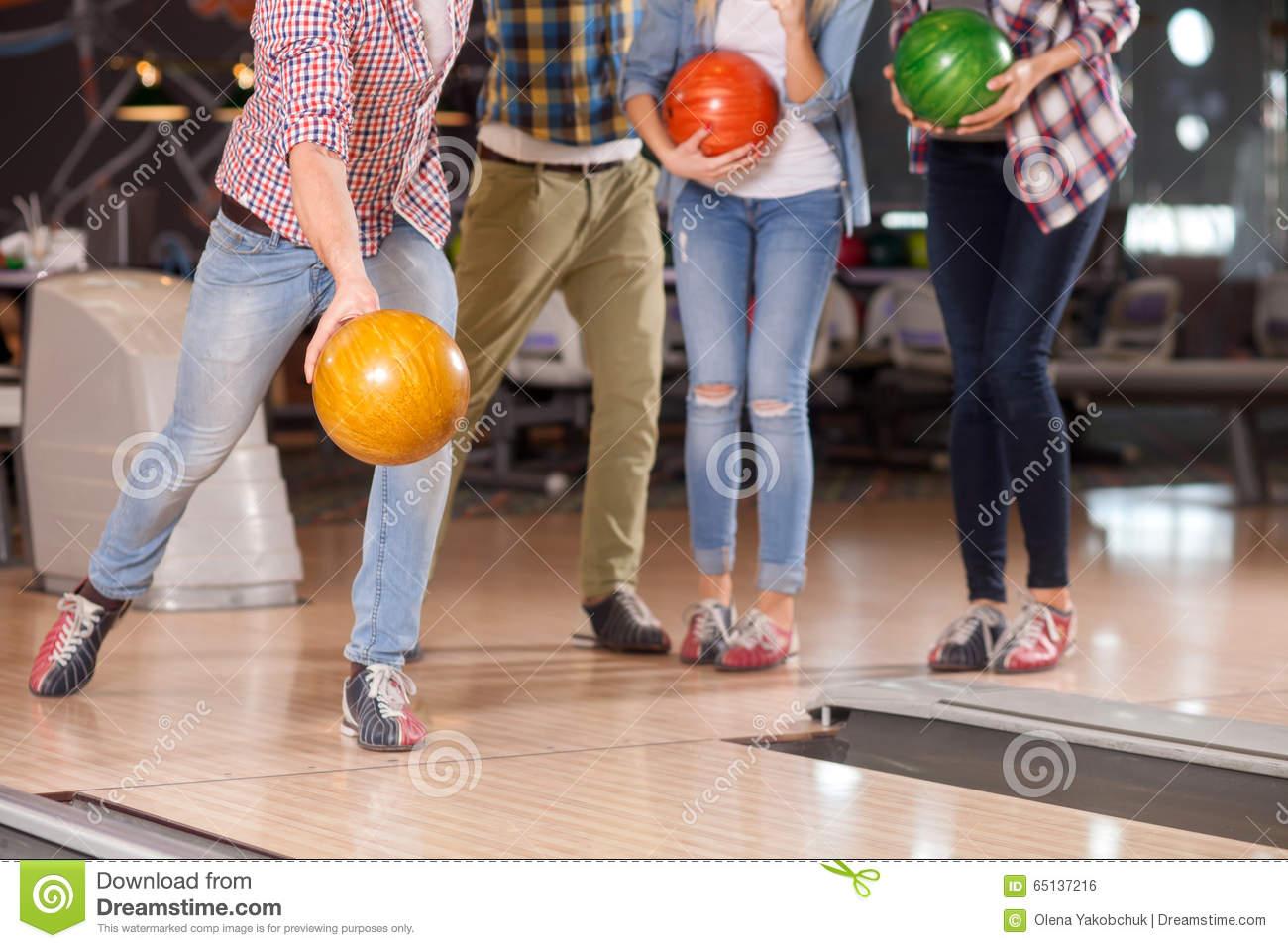 Los cuatro amigos lindos están jugando kegling juntos
