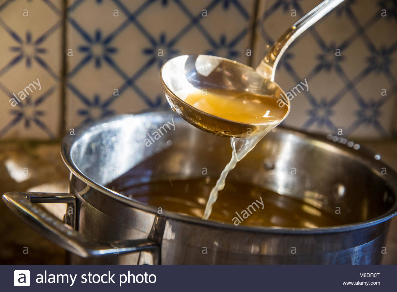 Broth being ladled from saucepan - Stock Image